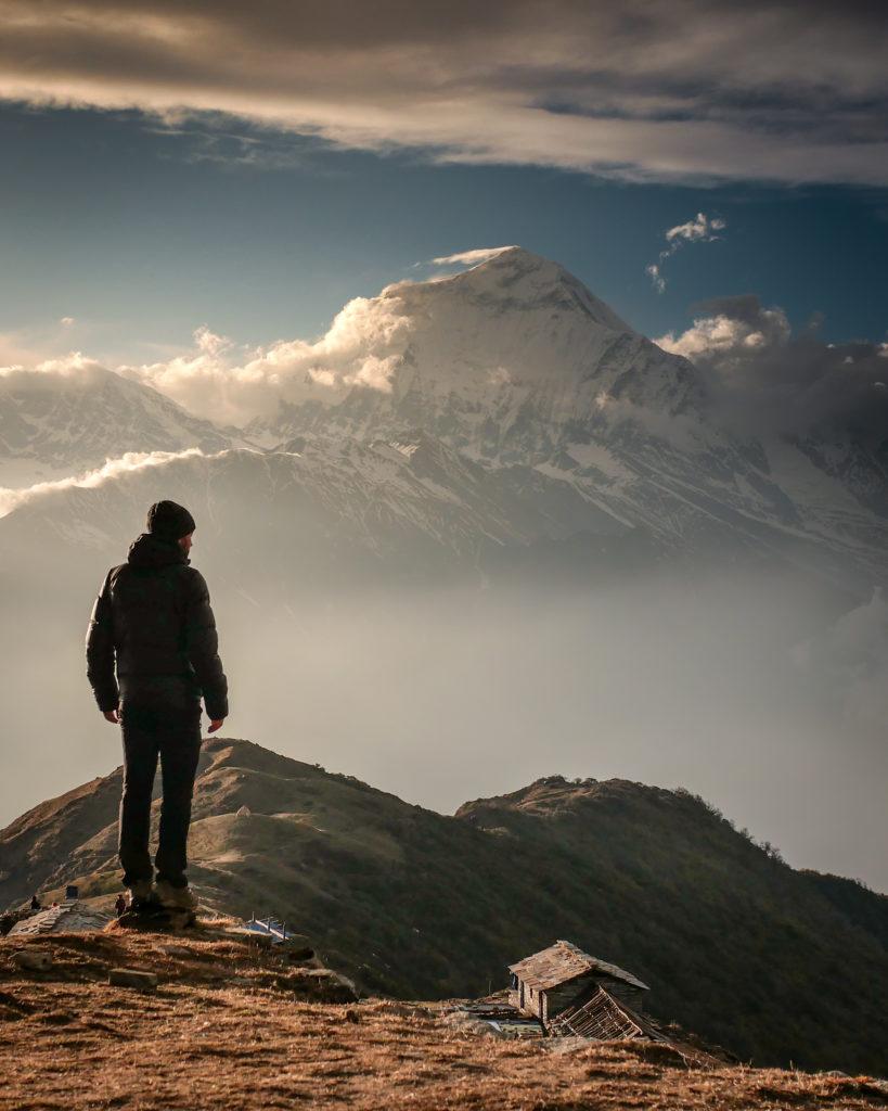 Homme face à la montagne, bergerie en contrebas
