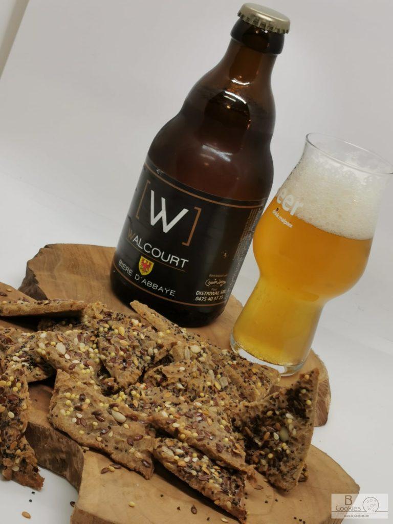 Planche en bois avec biscuits, verre de bière et bouteille