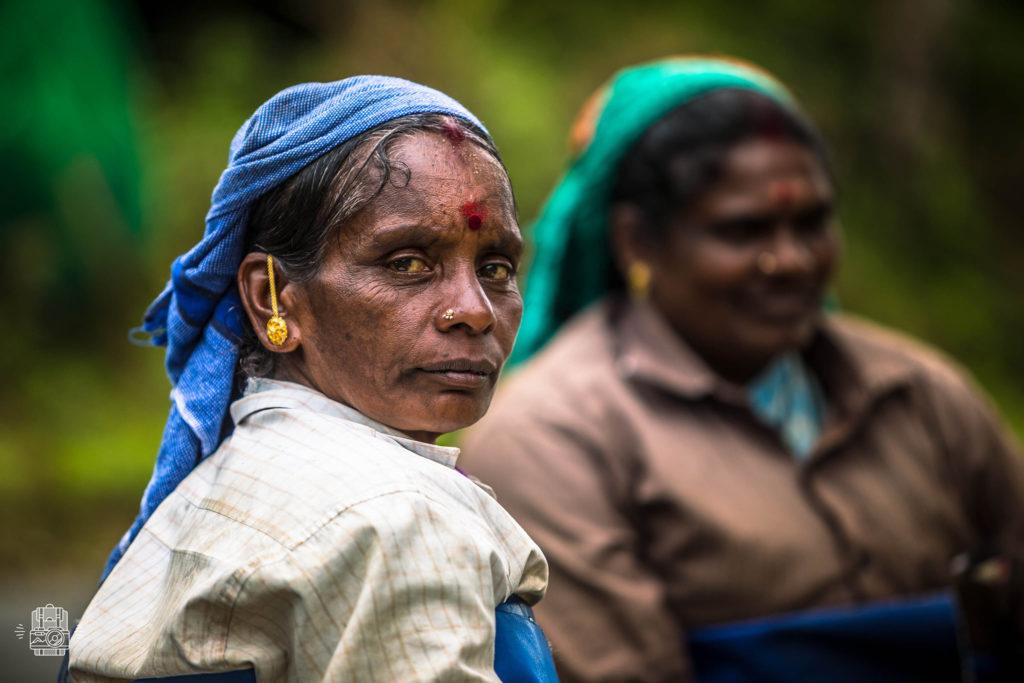 Femme foulard tête bijoux or rond rouge sur le front regarde objectif
