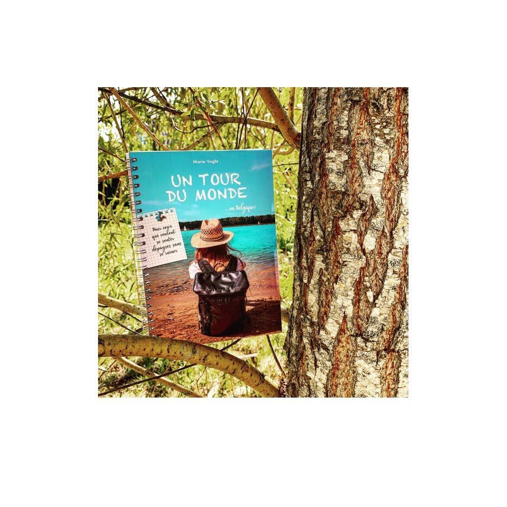 Photo du livre. Couverture femme avec chapeau et sac à dos assise au bord lac.  Fond de foret avec arbres branches