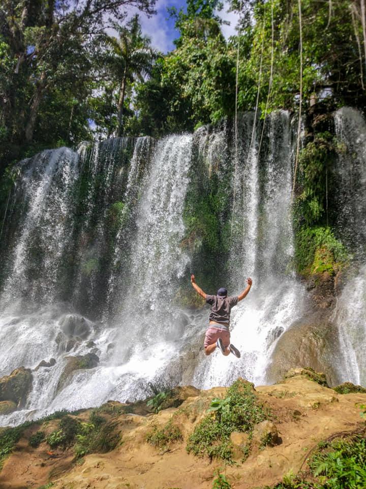 Homme saute devant cascade dans foret tropicale