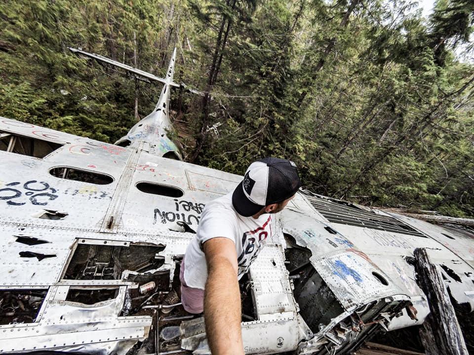 Homme sur carcasse avion dans foret