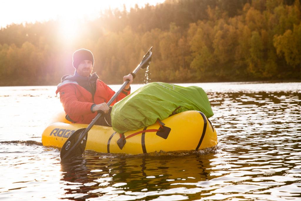 Homme en kayak jaune habillé en rouge, sac à dos vert sur le devant