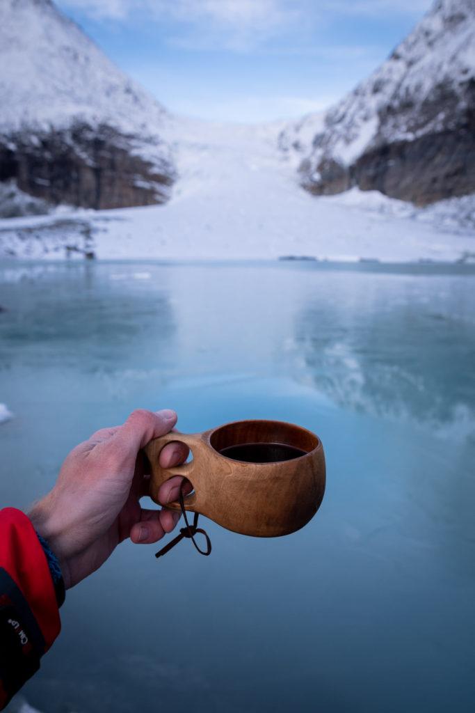 Main avec tasse de café rouge devant un lac, falaises enneigées en face