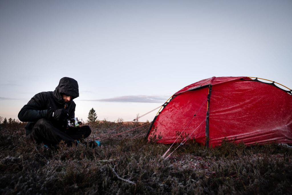 Homme en noir assis dans  la bruyère à coté de sa tente rouge