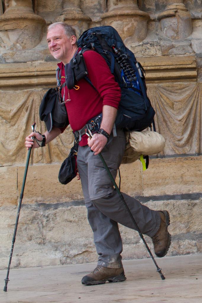 Homme marcheur bâtons de marche sac à dos devant église