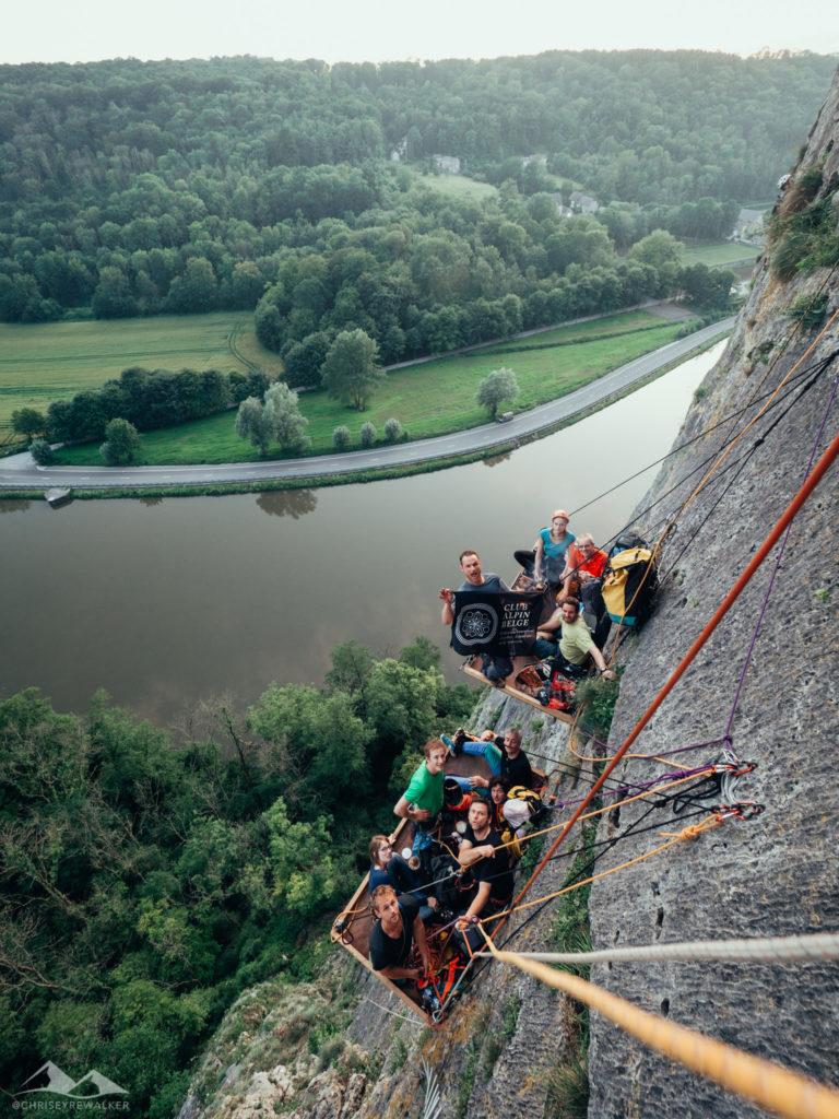 Phot groupe  grimpe falaise. Rivière, arbres et prairies en contre-bas. Drapeau club alpin belge.