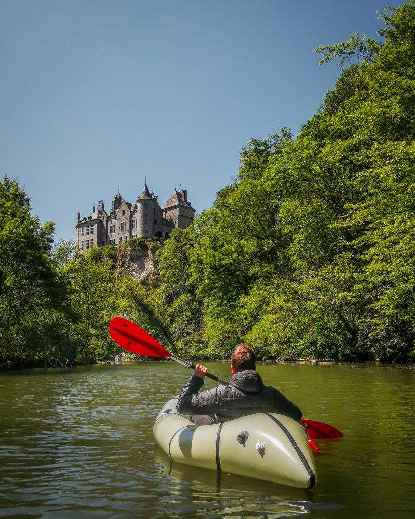 homme en kayak dans rivière arbres et château en hauteur