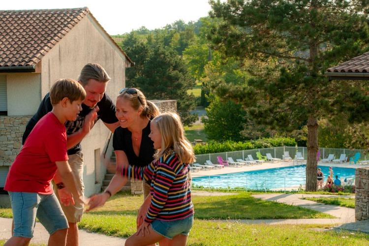 Famille dans village vacance en cercle jouent. Piscine à l'arrière