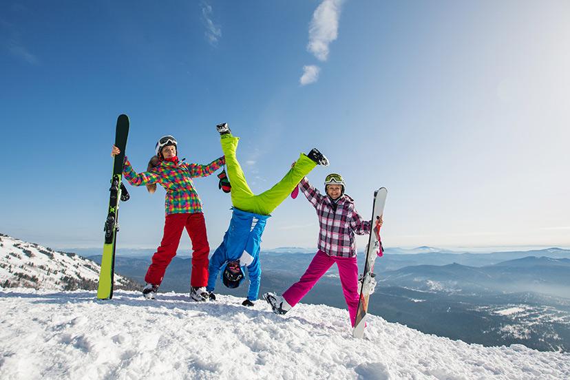 3 personnes au ski. Celui du milieu tête en bas les deux autres tiennent ses pieds