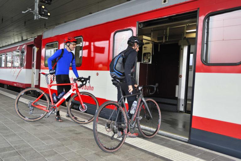 Personnes entrent dans un train rouge avec un vélo