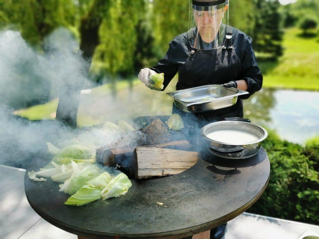 Traiteur cuit aliments sur feu, tenue noire et masque plastique Covid