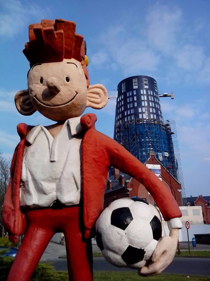 statute Spirou cheveux roux chapeau rouge tenue rouge ballon de football sous le bras devant tour de police de Charleroi
