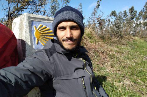 Selfie Tony Pana devant borne saint-jacques de Compostelle coquillage jaune tenue sport noire