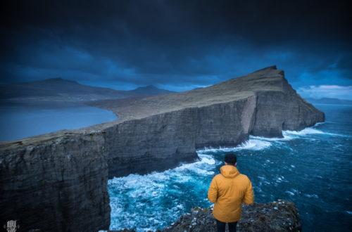 Homme sur falaise imperméable jaune ciel sombre