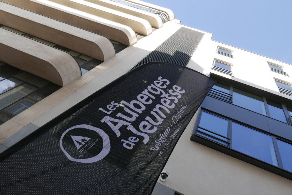 façade auberge jeunesse avec beach flag noir et logo blanc des auberges de jeunesse