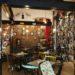café littéraire livre ou verre grandes bibliothèques bar chaises de récup multicolores cadres au mur du fond en brique