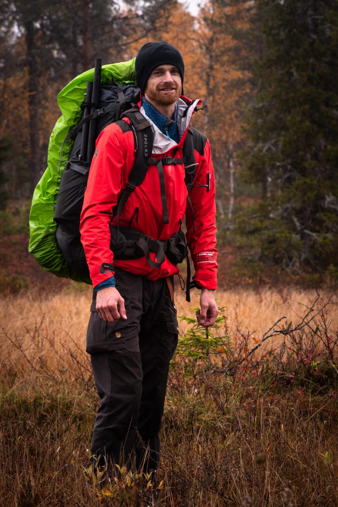 Homme tenue randonnée rouge et noire, sac à dos vert au milieu de la foret