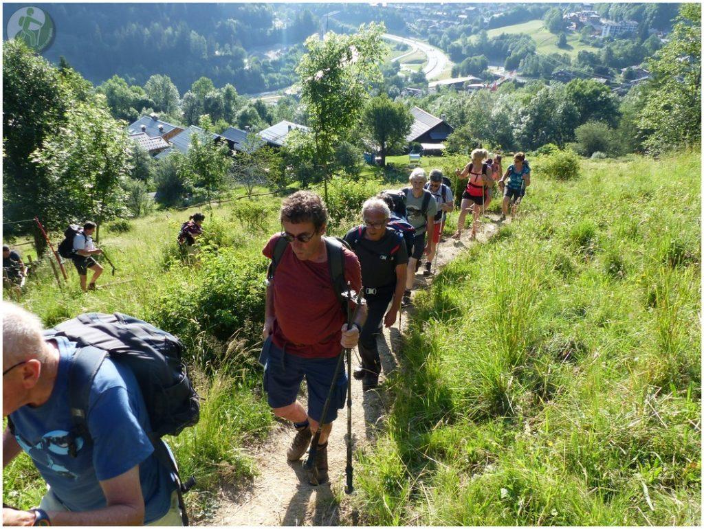 Groupe de randonnée dans montagnes. Marchent dans herbes hautes, village en contre-bas