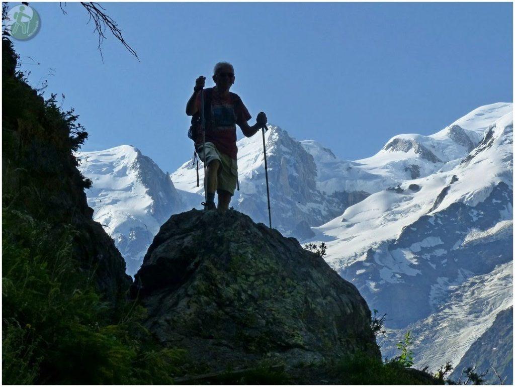 Homme sur rocher dos à montagnes enneigées