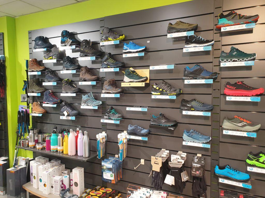 Mur vert présentoir noir chaussures randonnées gourdes  gants bâtons de marche