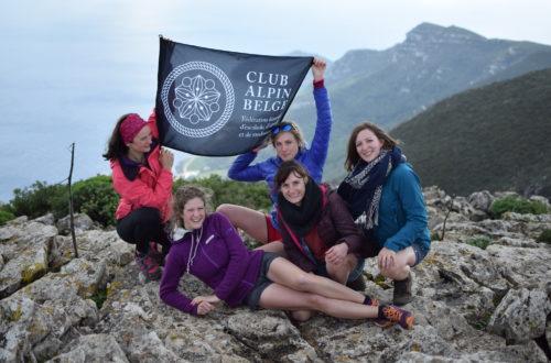Personnes au sommet d'une montagen avec drapeau noir écritures blanche club alpin belge