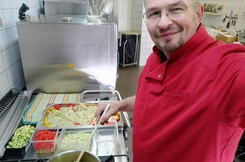 Homme chemise rouge lunettes dans cuisine