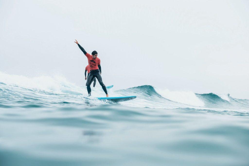 homme tenue rouge debout sur surf
