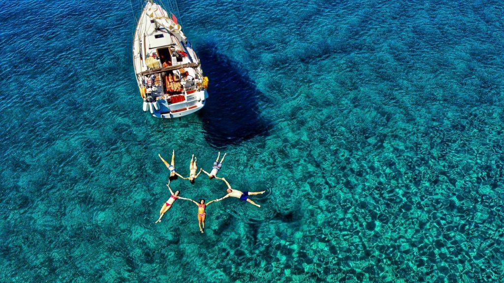 personnes se tiennent la main en rond dans mer bleue à coté d'un bateau