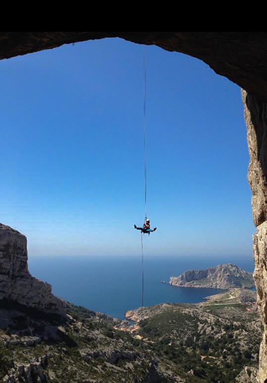 homme pend à une corde le long d'une falaise